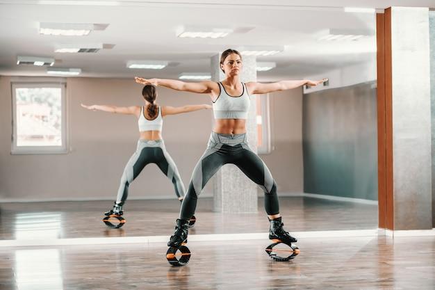 Jeune femme sportive en tenue de sport, faire des exercices de fitness avec des chaussures de sauts kangoo