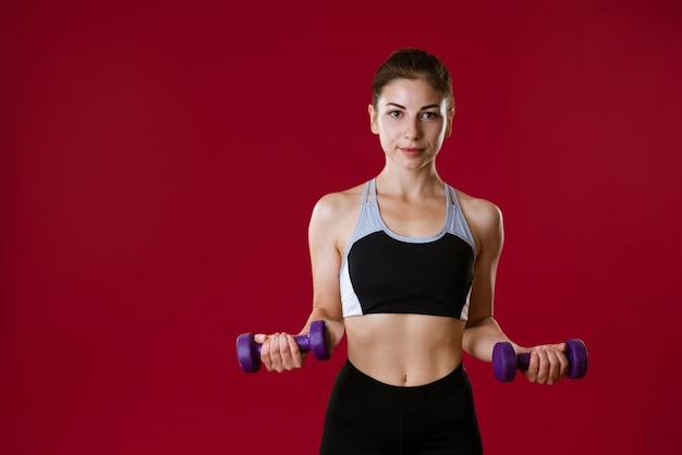 Jeune femme sportive en tenue de sport avec des haltères à la main sur un mur rouge