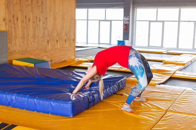 Jeune femme sportive sur un trampoline dans un parc de remise en forme et faisant de l'exercice à l'intérieur.