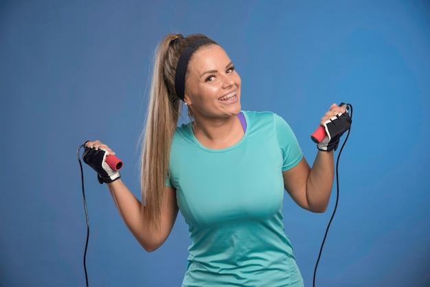 Jeune femme sportive travaillant avec des cordes à sauter.