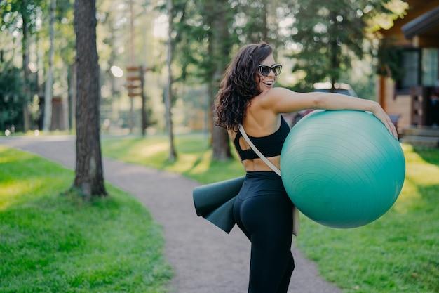 Jeune femme sportive travaillant à l'extérieur avec ballon