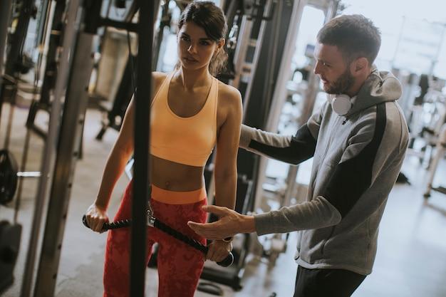 Jeune femme sportive travaillant sur une machine dans une salle de sport avec entraîneur personnel