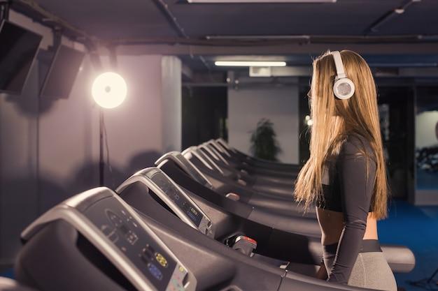 Jeune femme sportive travaille dans la salle de gym. faire de l'entraînement cardio sur tapis roulant.