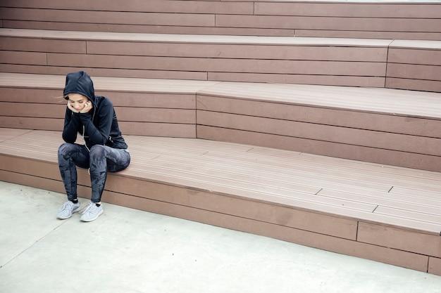 Jeune femme sportive triste et frustrée, assise en plein air