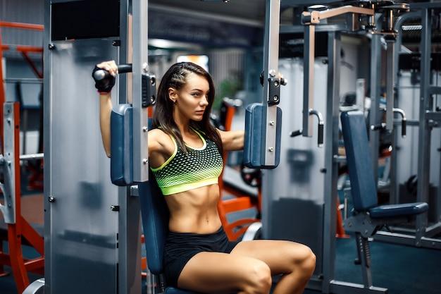 Jeune femme sportive utilisant une machine à mouches pectorales