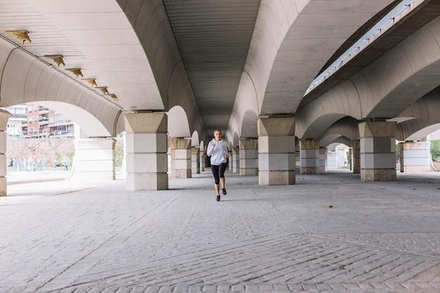 Jeune femme sprint sur la rue