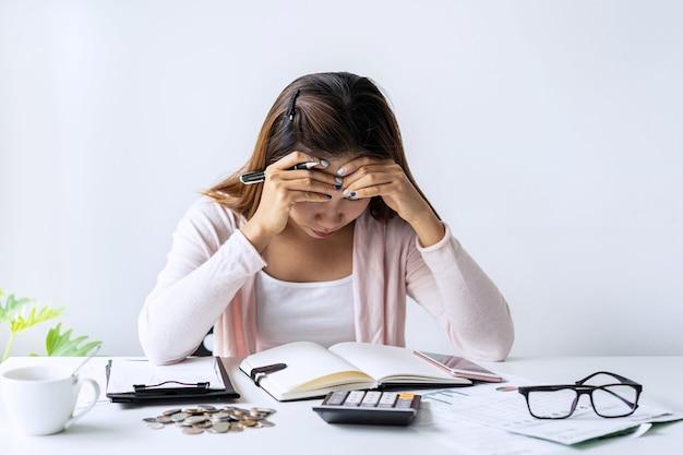 Jeune femme stressée, calcul des dépenses mensuelles à domicile