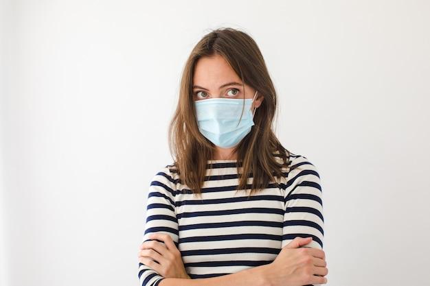 Jeune femme stressée mécontente en tenue décontractée et masque de protection pour la prévention des coronavirus debout, les bras croisés