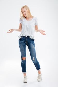Jeune femme stressée montrant des poches vides isolées sur un mur blanc