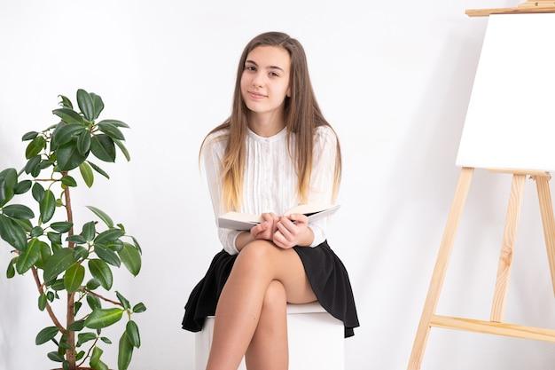 Jeune femme en studio d'art avec livre sur fond blanc