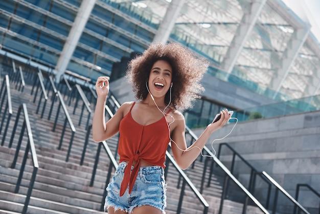 Jeune femme en style libre d'écouteurs dans la rue sautant sur sta