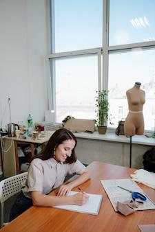 Jeune femme styliste travaillant sur ses créations en studio