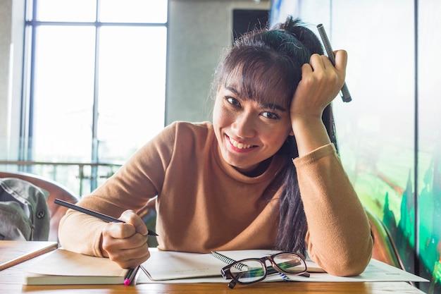 Jeune femme avec des stylos à la table