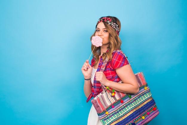 Jeune femme avec la sucette colorée au studio avec espace de copie