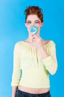 Jeune femme avec une sucette ou une sucette, elle a la dent sucrée