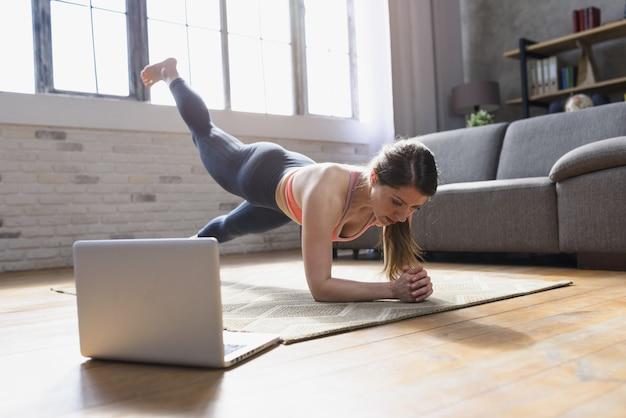 Jeune femme suit avec un ordinateur portable des exercices de gym.