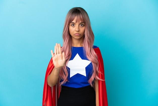 Jeune femme de super-héros aux cheveux roses isolée sur fond bleu faisant un geste d'arrêt