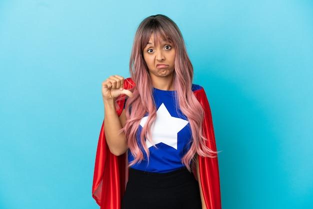 Jeune femme de super-héros aux cheveux roses isolée sur fond bleu montrant le pouce vers le bas avec une expression négative