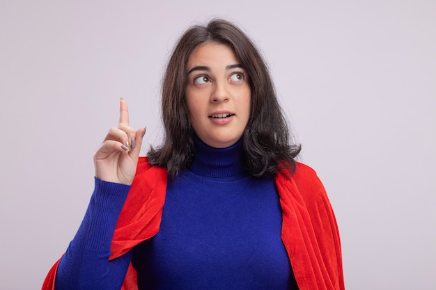Jeune femme de super-héros impressionnée en cape rouge regardant le côté pointant vers le haut isolé sur mur blanc