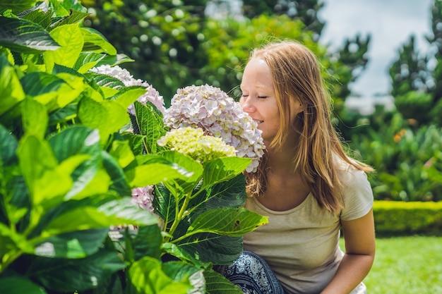 Jeune femme à la surface de fleurs d'hortensia rose clair qui fleurit dans le jardin