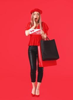 Jeune femme surprise avec un bon cadeau et des sacs à provisions