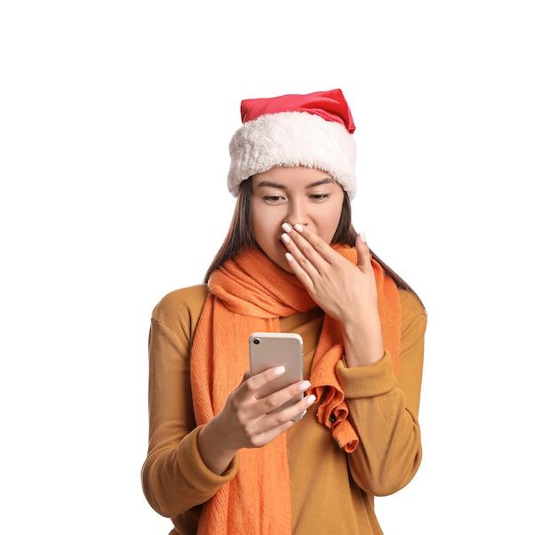 Jeune femme surprise en bonnet de noel et avec téléphone portable sur blanc