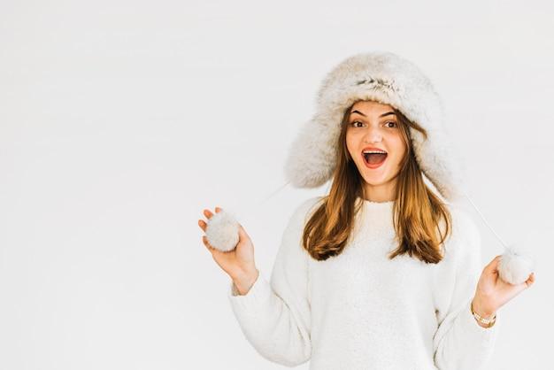 Jeune femme surprise en bonnet et pull de fourrure