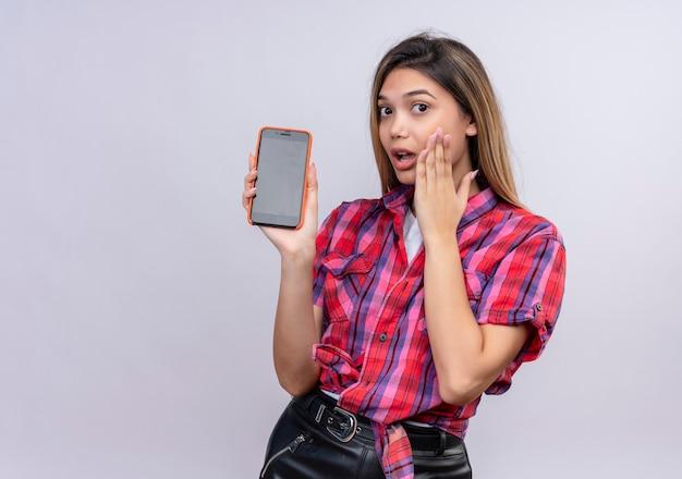 Une jeune femme surprise dans une chemise à carreaux montrant un téléphone mobile