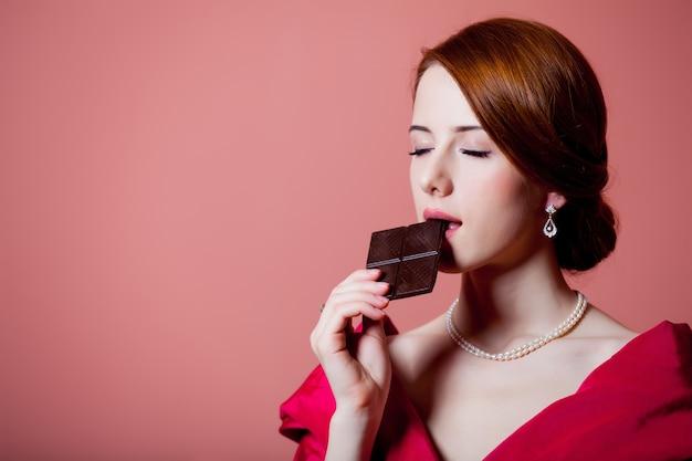 Jeune femme surprise dans des vêtements d'époque victorienne rouge avec du chocolat sur rose
