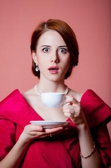 Jeune femme surprise dans des vêtements d'époque victorienne rouge avec une tasse de thé sur rose