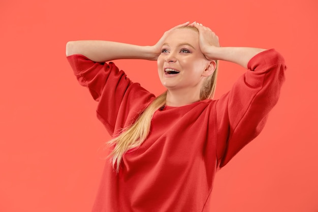 Jeune femme surprise émotionnelle debout avec la bouche ouverte