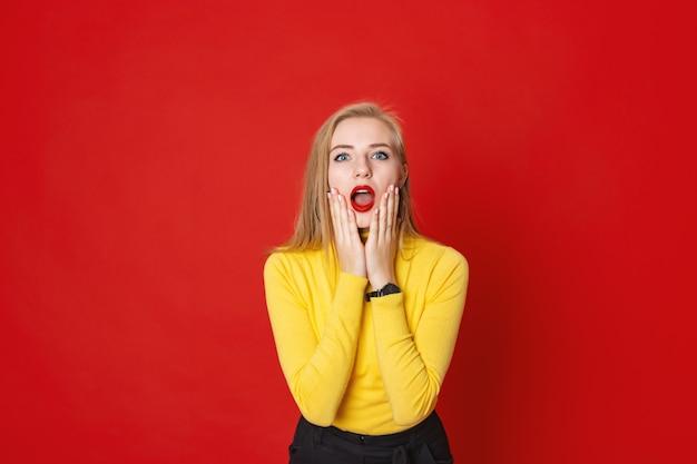 Jeune femme surprise est choquée avec la bouche ouverte