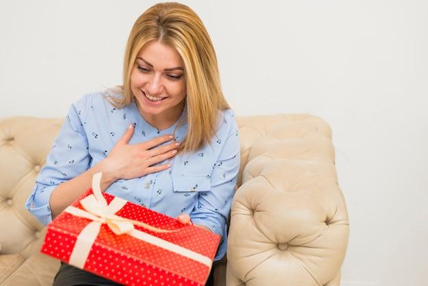 Jeune femme surprise heureuse avec boîte cadeau sur le canapé