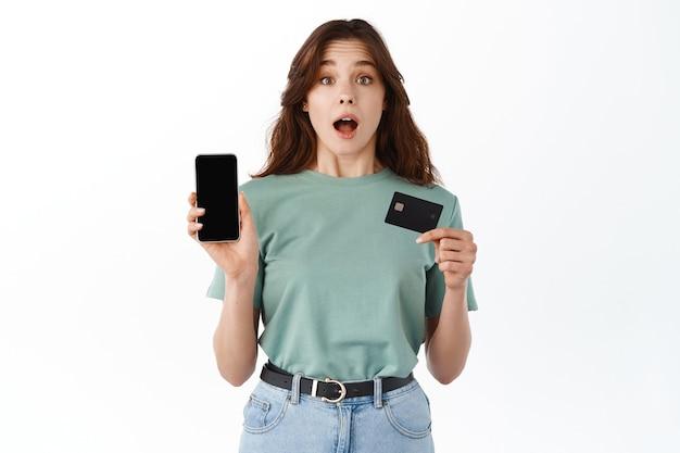 Jeune femme surprise montrant un écran de smartphone vide et une carte de crédit en plastique, démontre une application de banque mobile en ligne, debout contre un mur blanc