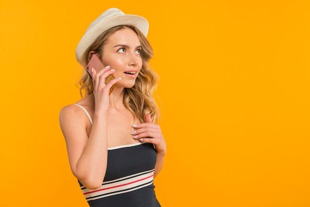 Jeune femme surprise parlant au téléphone