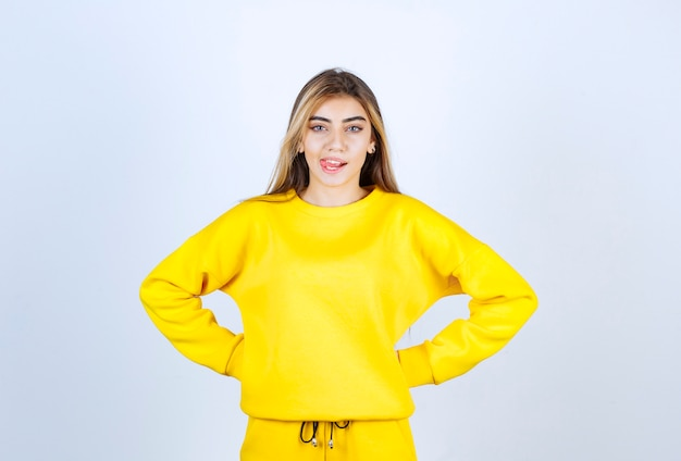 Jeune femme en survêtement jaune posant devant la caméra sur un mur blanc