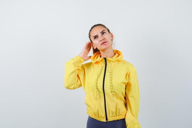 Jeune femme en survêtement avec la main derrière l'oreille et à la curieuse , vue de face.