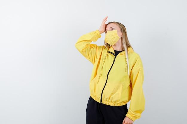 Jeune femme en survêtement, masque gardant la main sur la tête et à la fatigue, vue de face.