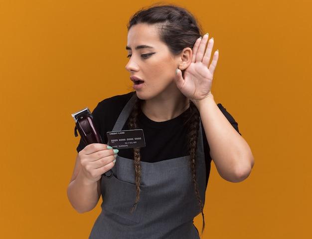Jeune femme suspecte coiffeur en uniforme tenant une carte de crédit et une tondeuse à cheveux montrant le geste d'écoute isolé sur un mur orange