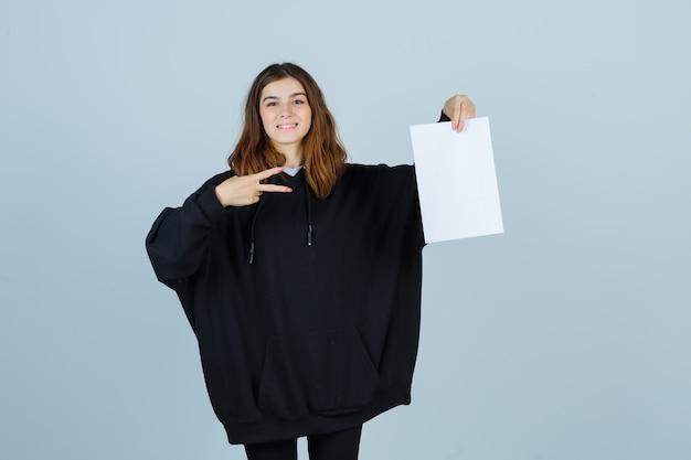 Jeune femme en sweat à capuche surdimensionné, pantalon montrant le signe de la victoire tout en tenant du papier et à la vue de face, heureux.