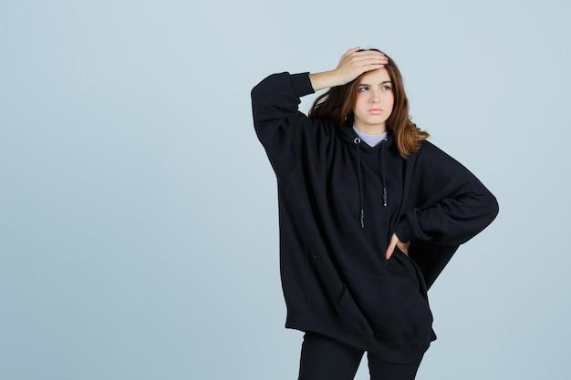 Jeune femme en sweat à capuche surdimensionné, pantalon tenant la main sur le front tout en gardant la main sur la taille et regardant oublieux, vue de face.