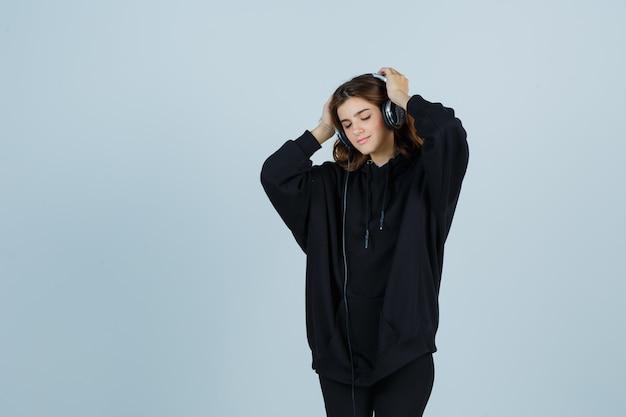 Jeune femme en sweat à capuche surdimensionné, pantalon tenant la main sur la tête tout en écoutant de la musique avec des écouteurs et à la vue de face, paisible.