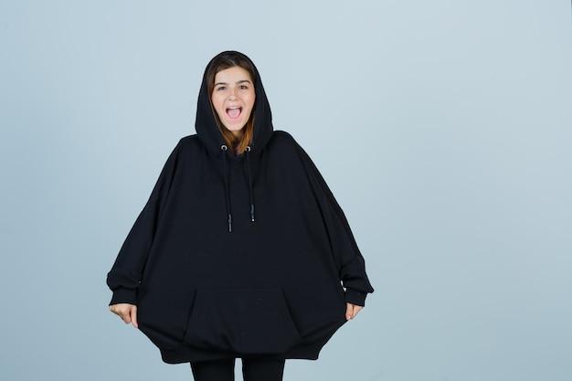 Jeune femme en sweat à capuche surdimensionné, pantalon tirant à capuche avec les mains et à la drôle, vue de face.