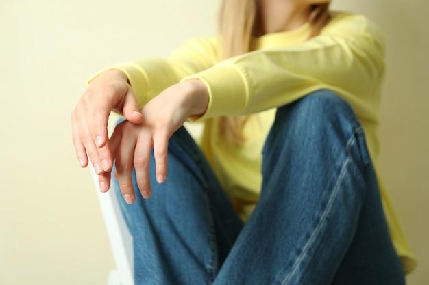 Jeune femme en sweat jaune assis contre beige