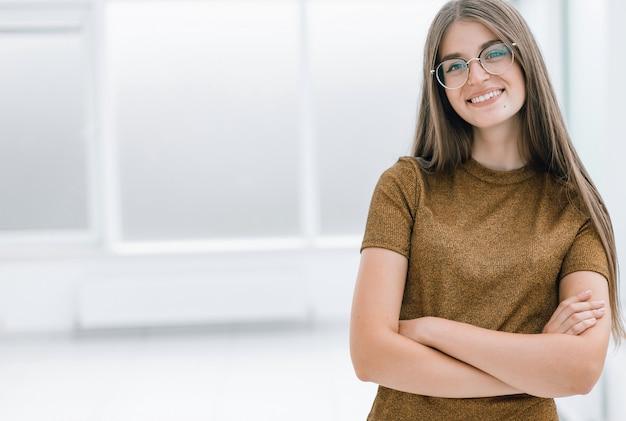 Jeune femme sympathique debout dans un bureau spacieux. photo avec espace copie