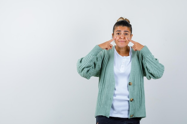 Jeune femme en t-shirt blanc et cardigan vert menthe gonflant les joues, pointant vers elle avec l'index et ayant l'air heureuse