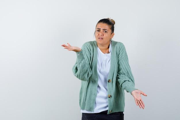 Jeune femme en t-shirt blanc et cardigan vert menthe s'étendant les mains de manière interrogative et l'air perplexe