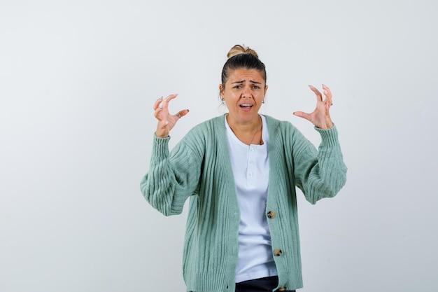 Jeune femme en t-shirt blanc et cardigan vert menthe tendant les mains comme tenant quelque chose et ayant l'air ennuyé