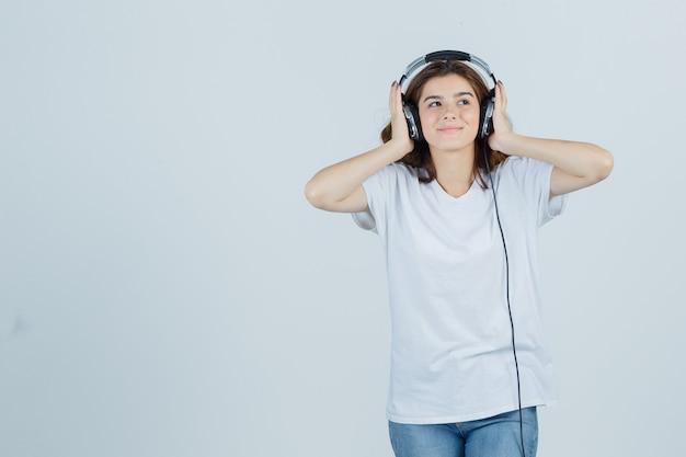 Jeune femme en t-shirt blanc, jeans appréciant la musique avec des écouteurs et à la joyeuse vue de face.