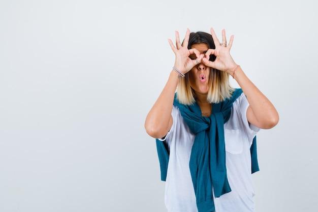 Jeune femme en t-shirt blanc montrant un geste de lunettes et l'air choqué, vue de face.